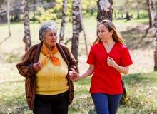 Ältere Frau und junge Pflegekraft lizenzfreies stockbild