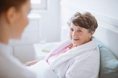 Ältere Frau und junger Freiwilliger am Pflegeheim lizenzfreie stockbilder