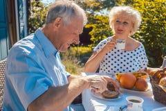 Ältere Frau und Mann, die sitzend in ihrem Garten frühstückt Stockfotografie