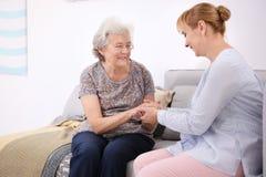Ältere Frau und Pflegekraft, die auf Sofa sitzt lizenzfreie stockfotos