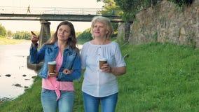 Ältere Frau und recht junges Mädchen geht entlang die Ufergegend und den trinkenden Kaffee Brücke und Weinlesewand des wilden Ste stock video footage