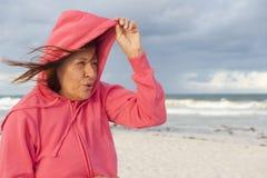 Ältere Frau und stürmisches Wetter am Strand Lizenzfreies Stockfoto
