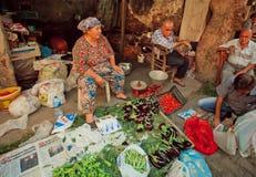 Ältere Frau verkauft Aubergine, Pfeffer und Tomaten auf rustikalem Straßenmarkt Stockfotos