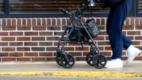 Ältere Frau verwendet einen Wanderer beim Gehen auf einen Bürgersteig nahe bei einem Gebäude stock footage