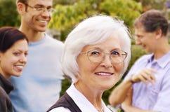 Ältere Frau vor Gruppe der jungen Leute Stockfotografie