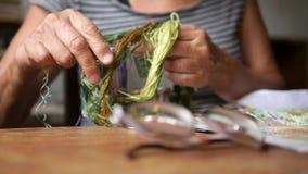 Ältere Frau wählt den Thread für Kreuzstich-Hobby vor 4K, Zeitlupe folgen Fokus stock video footage