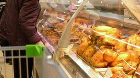 Ältere Frau wählt ein gebratenes Huhn auf der Anzeige in einem Supermarkt Leutekaufnahrungsmittel Kleinlebensmittelindustrie stock footage