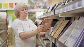 Ältere Frau wählt Foto oder Bilderrahmen im Supermarkt Einkauf im Speicher Ältere Frau sorgfältig stock video