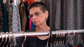 Ältere Frau wählt Kleid auf dem Speicher stock footage