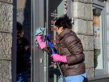 Ältere Frau wäscht die Glastüren des Speichers von der Straße Lizenzfreie Stockfotografie