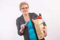 Ältere Frau, welche die Einkaufstasche und Kreditkarte, zahlend für den Einkauf hält stockbilder