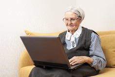 Ältere Frau, welche die Laptop-Computer sitzt auf Sofa verwendet Stockfotografie