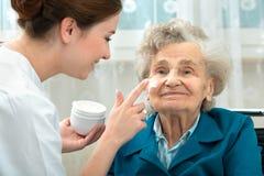 Ältere Frau wird von der Krankenschwester zu Hause unterstützt lizenzfreies stockbild