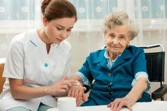 Ältere Frau wird von der Krankenschwester zu Hause unterstützt stockfoto