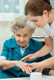 Ältere Frau wird von der Krankenschwester zu Hause unterstützt lizenzfreie stockfotos
