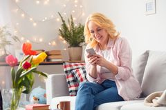 Ältere Frau zu Hause, die Grasen Smartphone froh sitzt stockfoto