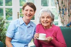Ältere Frau zu Hause mit Betreuer lizenzfreie stockbilder