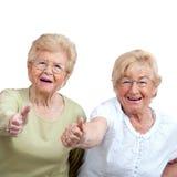 Ältere Frau zwei, die sich Daumen zeigt. Lizenzfreie Stockfotografie