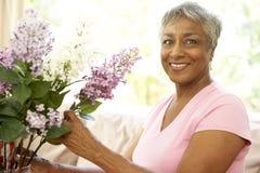 Ältere Frauen-Blume, die zu Hause anordnet Lizenzfreies Stockfoto