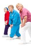 Ältere Frauen, die Fahrwerkbeine streching sind. Stockfoto