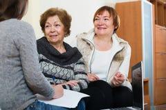Ältere Frauen, die mit Bankwesenmittel sich beraten stockbild