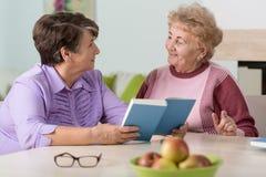 Ältere Frauen, die am Tisch sitzen Stockbilder