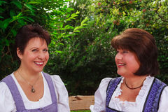 Ältere Frauen, die zusammen in einem bayerischen Dirndl auf einer Bank im Garten sitzen Lizenzfreie Stockfotografie