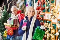Ältere Frauen-Einkaufsweihnachtsverzierungen am Speicher lizenzfreie stockfotografie