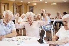 Ältere Frauen-gewinnendes Spiel von Bingo im Ruhesitz stockbilder
