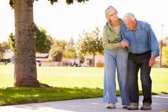 Ältere Frauen-helfender Ehemann, wie sie in Park zusammen gehen Lizenzfreie Stockbilder