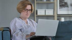 Ältere Frauen-on-line-Videochat auf Laptop bei der Arbeit stock video footage