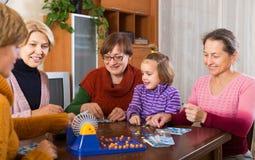 Ältere Frauen mit Kind am Schreibtisch mit Bingo Lizenzfreie Stockfotos