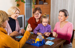 Ältere Frauen mit Kind am Schreibtisch mit Bingo Stockfotografie
