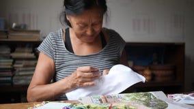 Ältere Frauen-nähendes Kreuzstich-Bild auf weißem Baumwollstoff 4k, Zeitlupe stock footage
