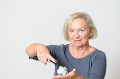Ältere Frauen-Vertretung zerknittertes verfügbares Geld Stockbild