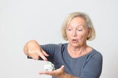 Ältere Frauen-Vertretung zerknittertes verfügbares Geld Stockfotos