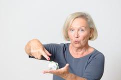 Ältere Frauen-Vertretung zerknittertes verfügbares Geld Stockfoto