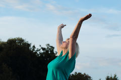 Ältere Frauenarme zum Himmel Stockfotografie