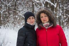Ältere Frauenmutter mit Tochter im Winter im hölzernen Lächeln des Schnees Stockfotos