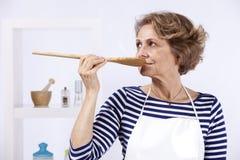 Ältere Frauenprobierennahrung Lizenzfreie Stockfotografie