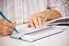 Ältere Frauenschreibenschecks Lizenzfreie Stockfotografie