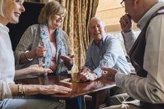 Ältere Freunde, die Dominos spielen lizenzfreies stockbild
