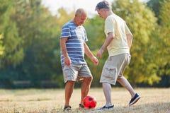 Ältere Freunde, die Fußball spielen stockbilder