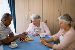 Ältere Freunde, die Schach spielen und Kaffee trinken Stockbilder
