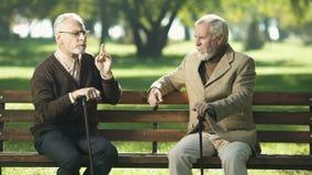 Ältere Freunde, die, sitzend auf Bank im Park, glückliche Gedächtnisse sprechen und lachen stock video