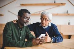Ältere Freunde, die Smartphone betrachten Stockbilder