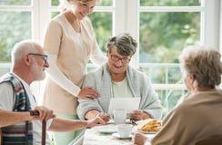 Ältere Freunde, die zusammen Zeit am Pflegeheim verbringen stockfotografie