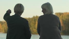Ältere Freundinnen, die auf Flussbank, werfende Steine, Landschaftsrest sitzen stock video footage