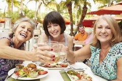 Ältere Freundinnen, die Mahlzeit Restaurant im im Freien essen stockfotos