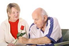 Ältere gebende Frau des Handikaps eine Rose stockfoto